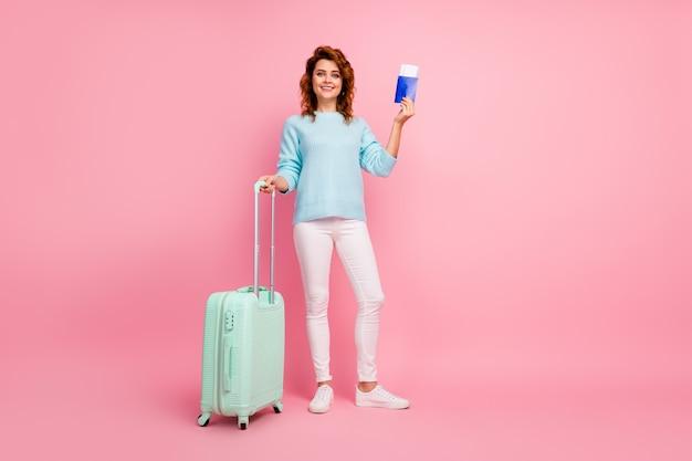 Vista de corpo inteiro dela, ela é bonita, atraente, adorável, alegre, de cabelos ondulados, segurando a bagagem de mão em uma viagem de passaporte isolada sobre um fundo rosa pastel