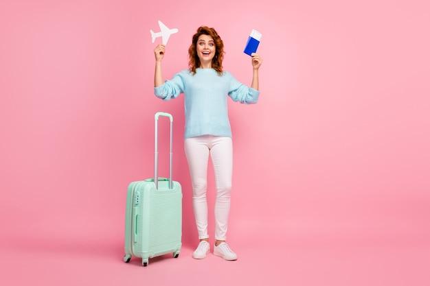 Vista de corpo inteiro dela, ela é legal, atraente, alegre, alegre, alegre, garota de cabelos ondulados segurando nas mãos uma passagem de avião de papel, passando o feriado isolado sobre um fundo de cor rosa pastel