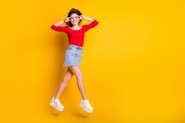 Vista de corpo inteiro dela, ela é legal, atraente, alegre, alegre, menina magra, pulando se divertindo, mostrando o sinal v isolado sobre fundo de cor amarela vibrante de brilho vívido brilhante