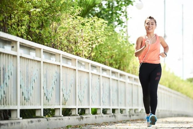 Vista de corpo inteiro do jovem atleta fazendo uma corrida matinal sozinha