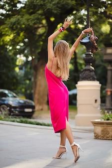 Vista de costas, altura total, elegante mulher atraente com vestido rosa sexy de verão, caminhando na rua, segurando uma bolsa feliz