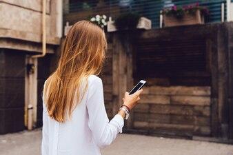 Vista, de, costas, de, elegante, mulher, com, longo, loiro cabelo, usando, um, telefone móvel