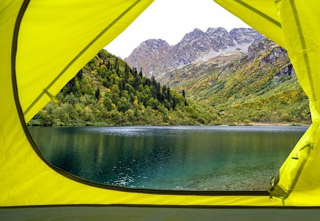 Vista de dentro da barraca de acampamento amarela no lago e na madeira da montanha. fundo de viagem