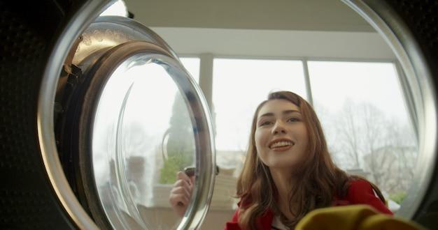 Vista de dentro da máquina de lavar roupa na linda mulher feliz caucasiana, abrindo e tirando a roupa lavada limpa. close-up da encantadora garota alegre em uma lavanderia pública