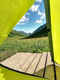 Vista de dentro de uma barraca de acampamento amarela nas montanhas