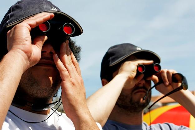 Vista de dois usuários binoculares com os chapéus que olham algo.