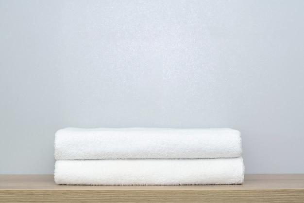 Vista de duas toalhas de banho brancas cuidadosamente dobradas em uma prateleira de madeira.