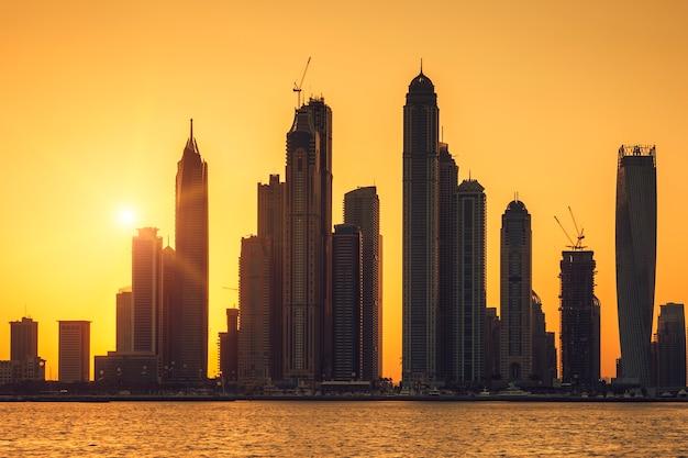 Vista de dubai com sol ao nascer do sol, emirados árabes unidos.