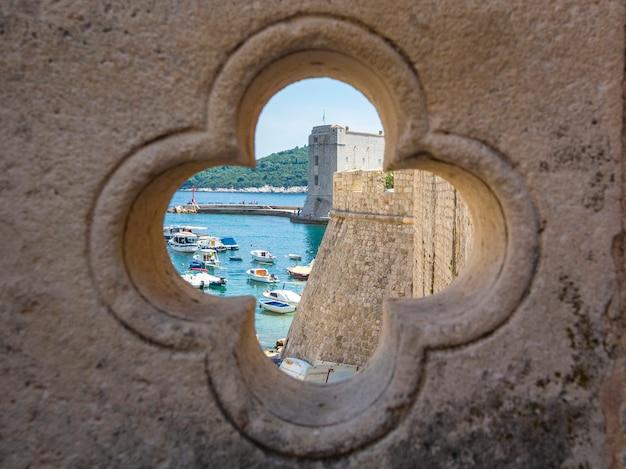 Vista de dubrovnik na cidade velha, paredes de pedra, mar e barcos através do trevo da sorte trevo, dalamtia, croácia
