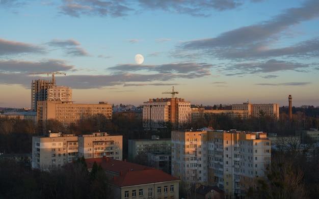 Vista de edifícios residenciais por do sol com céu nublado. a lua como visto entre edifícios e canteiros de obras ao pôr do sol na cidade de lviv, na ucrânia.