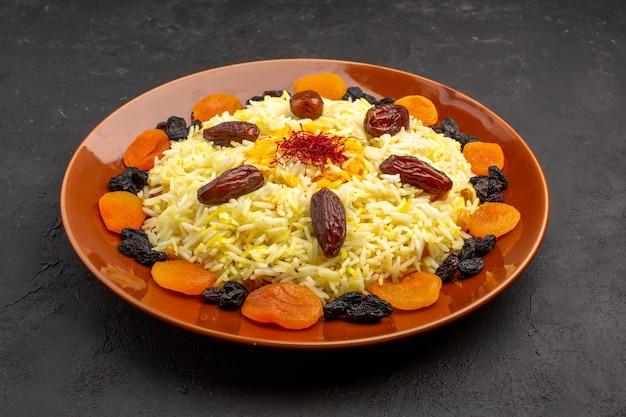 Vista de frente, a saborosa refeição oriental famosa de plov consiste em arroz cozido e diferentes passas no espaço escuro