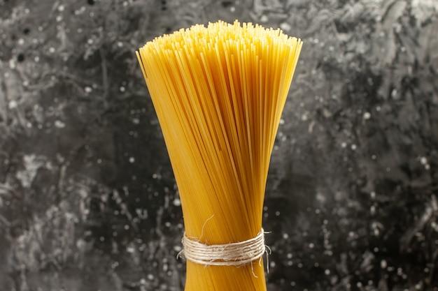 Vista de frente da massa italiana longa crua na refeição de fotos de cozinha de massa de cor cinza claro