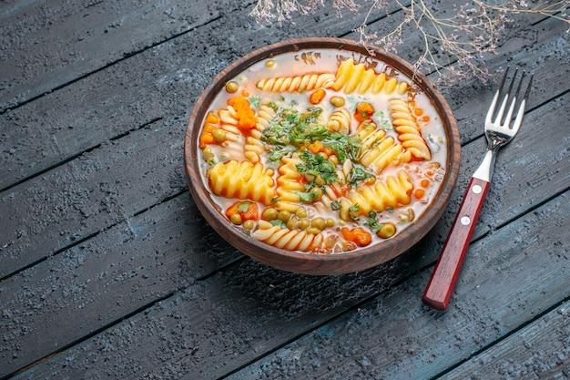 Vista de frente deliciosa sopa de massa italiana em espiral com verduras na mesa rústica escura prato de jantar molho de sopa de massa italiana