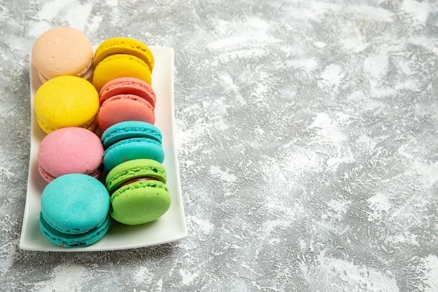 Vista de frente macarons franceses bolos coloridos na superfície branca torta de bolo açúcar asse biscoito biscoitos doces