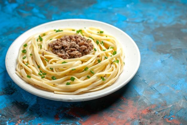 Vista de frente saborosa massa italiana com verduras e carne moída na cor azul do prato de massa