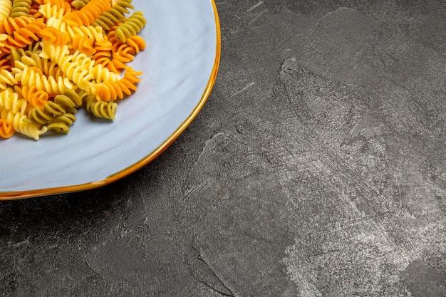 Vista de frente saborosa massa italiana incomum massa espiral cozida em prato cinza de mesa cozinhando massa colorida