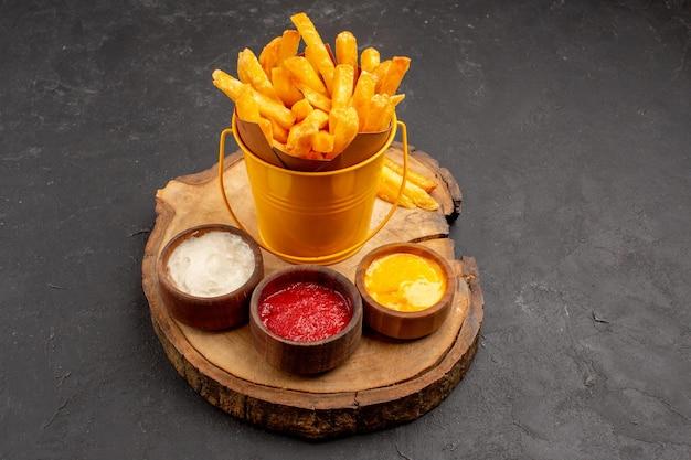 Vista de frente saborosas batatas fritas com molhos em espaço escuro