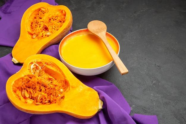 Vista de frente, sopa simples de abóbora em tecido roxo e mesa escura jante suavemente no dia de ação de graças