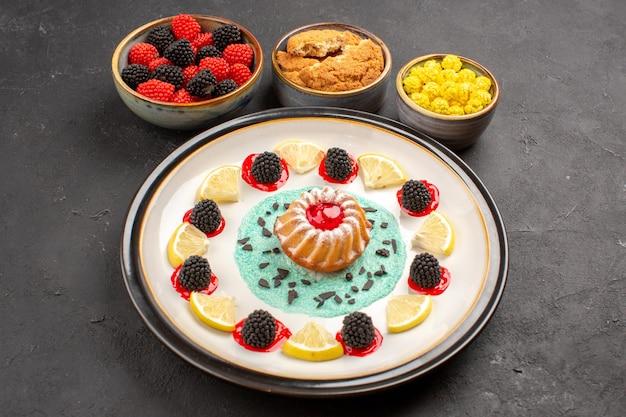 Vista de frente um pequeno bolo gostoso com rodelas de limão e doces no fundo escuro