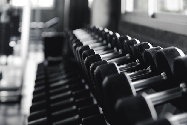 Vista de fundo para trás e halteres de equipamento branco em rack no centro de esporte de ginásio
