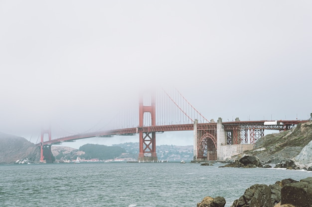 Vista de golden gate bridge no nevoeiro da praia próxima.