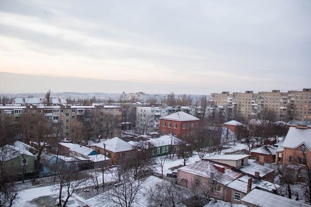 Vista de inverno da janela de um prédio de apartamentos com casas antigas e modernas
