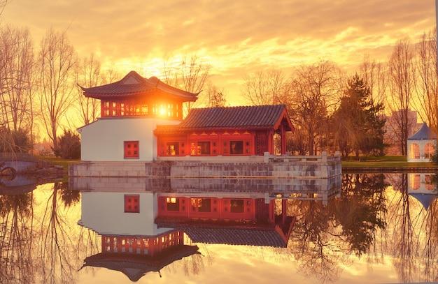 Vista de inverno do jardim formal chinês com pavilhão decorativo refletido na lagoa