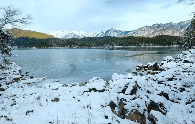 Vista de inverno do lago eibsee com fina camada de gelo na superfície da água, baviera, alemanha.