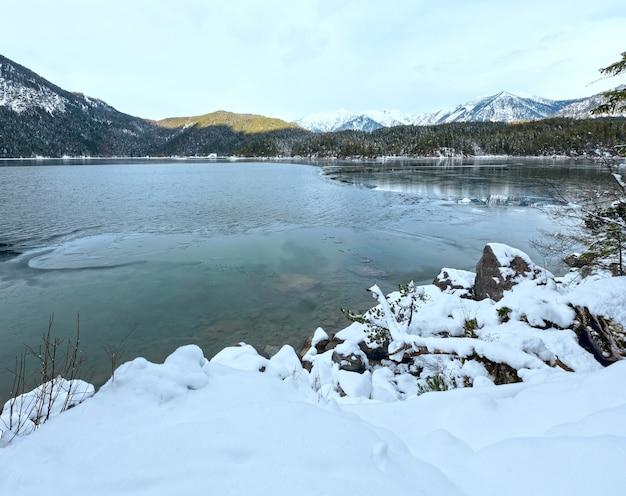 Vista de inverno do lago eibsee com fina camada de gelo na superfície e monte de neve, baviera, alemanha.