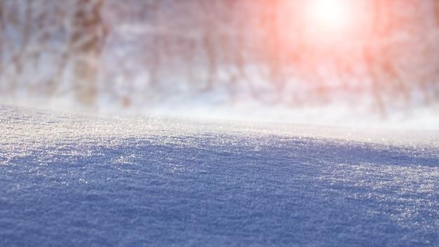 Vista de inverno, plano de fundo de natal. terreno coberto de neve em um fundo de floresta de inverno pela manhã durante o nascer do sol