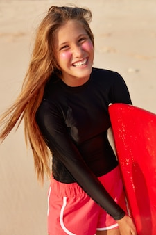 Vista de jovem europeu de aparência agradável, com corpo perfeito, cabelo comprido e reto, sorrisos largos