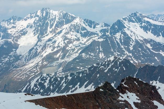Vista de junho da montanha dos alpes karlesjoch (3.108 m, perto de kaunertal gletscher, na fronteira da áustria-itália) sobre o precipício e as nuvens.