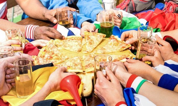 Vista de lado superior das mãos multirraciais de torcedor de amigos de futebol compartilhando pizza margherita no restaurante