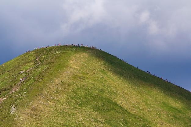Vista de longe iluminada pela montanha do sol de verão hoverla com muitas pessoas viajando para cima e para baixo pela rota turística sob o céu azul brilhante. beleza da natureza, perigo para a ecologia, turismo e caminhadas conceito.