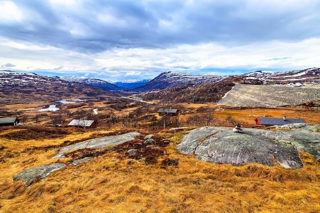 Vista de longe sobre as casas no meio de campos e montanhas