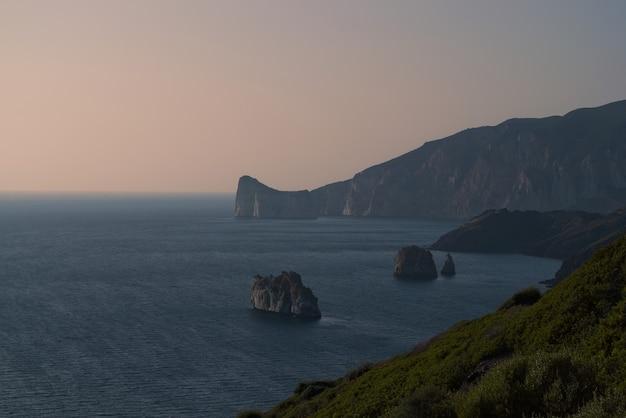 Vista de manhã cedo de um litoral panorâmico de porto corallo em nebida, itália