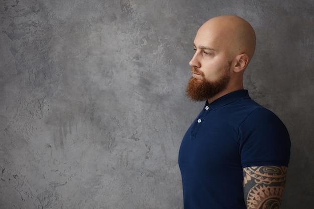Vista de meio perfil de um hipster caucasiano elegante e bonito com cabeça raspada e barba longa e espessa posando contra uma parede branca e cinza com espaço de cópia para seu conteúdo de publicidade