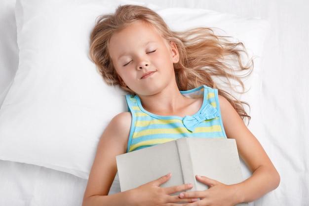 Vista de menina adorável com cabelo longo e claro dorme depois de ler o conto de fadas, mantém o livro no estômago, encontra-se na confortável cama branca, tem sonhos agradáveis, gosta de conto de fadas. crianças e conceito de relaxamento