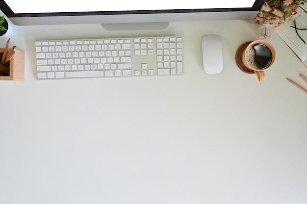 Vista de mesa de trabalho com computador e equipamentos, café, lápis com flor, cabeçalho do herói.