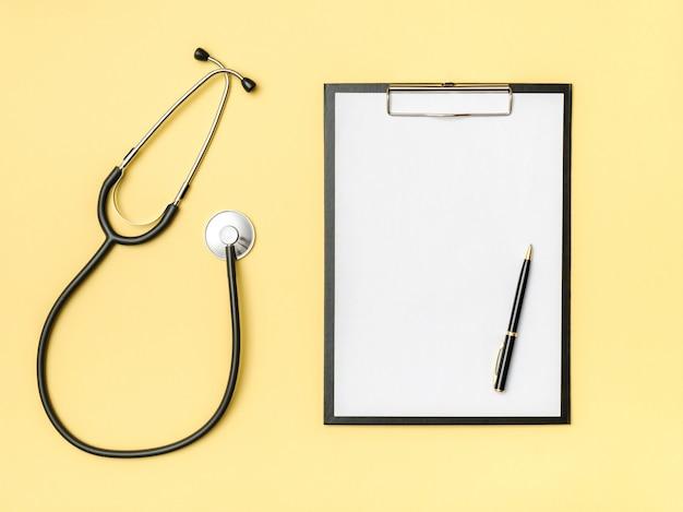 Vista de mesa do médico. estetoscópio e caderno em um fundo colorido