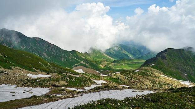 Vista de montanhas cobertas de neve e céu nublado em sochi, verão na rússia