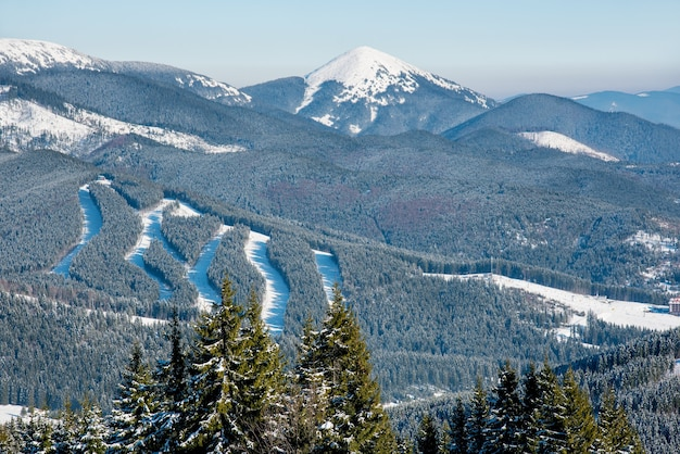 Vista de montanhas nevadas, florestas e pistas de esqui em um dia ensolarado de inverno
