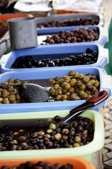 Vista de muitos baldes cheios com muitos tipos de azeitonas, incluindo verdes, negros e marrons em um mercado.