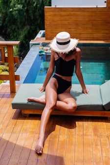 Vista de mulher de pele perfeita bronze muito bronzeada em biquíni preto vintage velho encontra-se na espreguiçadeira verde na villa incrível em dia ensolarado, descansando, curtindo as férias.