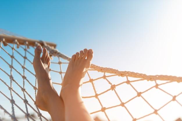 Vista de mulher relaxando na rede. visão de baixo ângulo. pés femininos bonitos relaxando em uma rede.