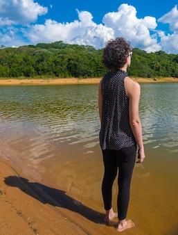 Vista de mulher relaxante olhando para o lago.