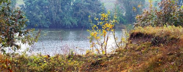 Vista de outono com um penhasco perto do rio e árvores e arbustos coloridos na costa