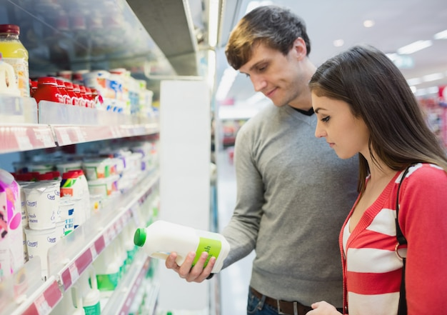 Vista de perfil de casal fazendo compras na mercearia