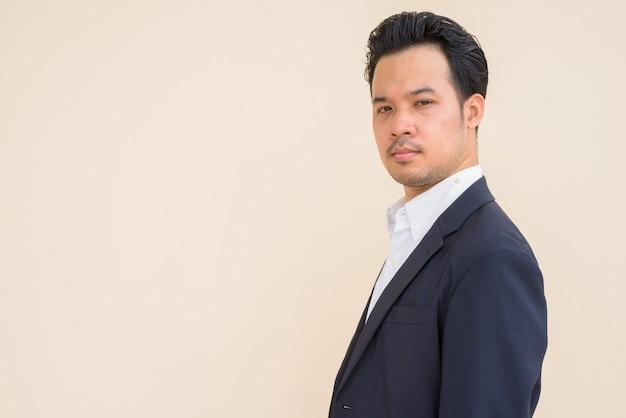 Vista de perfil de empresário asiático vestindo terno contra um fundo simples