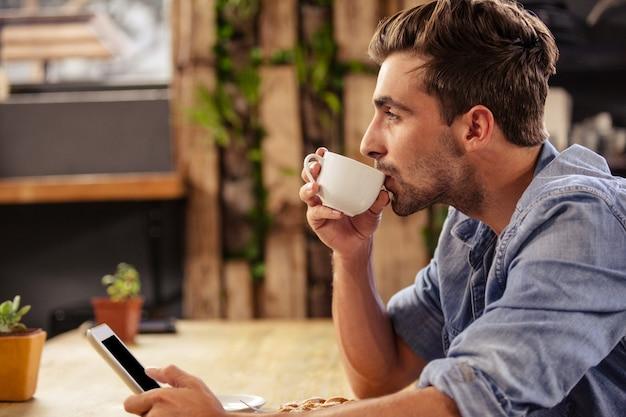 Vista de perfil de homem hipster usando tablet no café